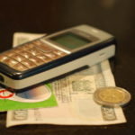 mobile phone money - Erik (HASH) Hersman Mobile Phone with Money in Kenya - CC BY 2.0